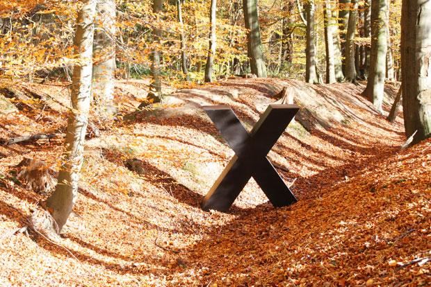 Ein großes, massives, schwarzes X, fast mannshoch, steht in einem sonnigen Herbstlaubwald neben einem Bodenwall.