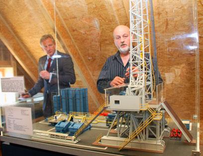 Zwei Männer unter einer Dachschräge hinter einem auf einem Tisch aufgebauten Modells einer Öl-Förderanlage.