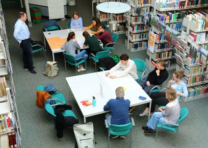 Draufsicht auf arbeitende Menschen an 2 großen quadratischen grauen Tischen, die zwischen lauter grauen metallenen gefüllten Bücherregalen sitzen.