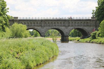 Bräunlicher Fluss mit grasbewachsener grüner Böschung mit einzelnen Büschen. Über den Fluss wölbt sich eine graue steinerne Brücke mit 3 Bogen und einem schwarzen metallenen Handlauf auf den Seitenwänden.
