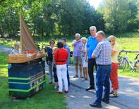 Menschen stehen teils auf einem asphaltierten Weg, teils auf der anschließenden Wiese neben einem dunkelblauen Kubus mit grünen Steifen auf dem das Modell eines Bootes aus Holz mit einem großen, dreieckigen braunen Segel zu sehen ist. Rechts im Hintergrund Bäume und ein an einen Weidezaun gelehntes Fahrrad.