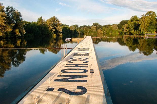 """Ein sehr langer Holzsteg führt zentral über einen See. Der See ist unregelmäßig geformt und von Bäumen umstanden. Auf der Seeoberfläche spiegelt sich der blaue Himmel mit Wolken. Auf dem Holzsteg ist in schwarzen Blockbuchstaben die Frage: """"Bin ich schön?"""" zu lesen."""