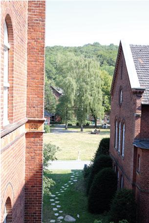 Blick zwischen zwei Häuserfronten aus rotem Backstein zeigt gewundenen Pfad aus doppelreihige angeordneten Trittsteinen auf einer grünen Wiese.