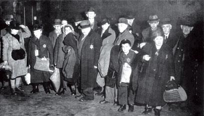 """18 Personen, darunter ein Kind, eng beieinanderstehend mit Taschen und Beuteln in den Händen, mehrheitlich mit Hüten auf dem Kopf. Auf der linken Brust eingenähte """"Judensterne""""."""