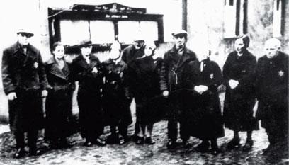 Zehn Personen in Mänteln, einige Blicken in die Kamera, einige daneben.