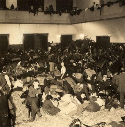 Großer Raum, im hinteren Eck viele Stühle auf einem Haufen, davor Menschen liegend oder sitzend auf Stroh oder Decken.