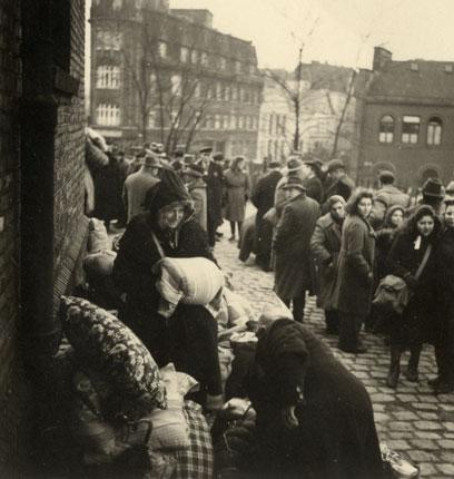 Links zwei Personen vor einer Gebäudemauer mit Kissen und Decken, dahinter Menschenmenge, einige schauen auf die Personen.
