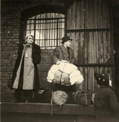 Drei Personen vor einer Mauer eines Gebäudes mit großem Fenster und großem Tor, ein Mann hält Bettzeug in den Händen, an den Füßen liegt Gepäck.