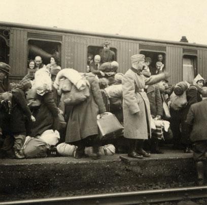 Vollbesetzter Zug, Kinder und Erwachsene schauen aus dem Fenster, davor ein uniformierter Mann und viele Menschen mit Bettzeug und Taschen.