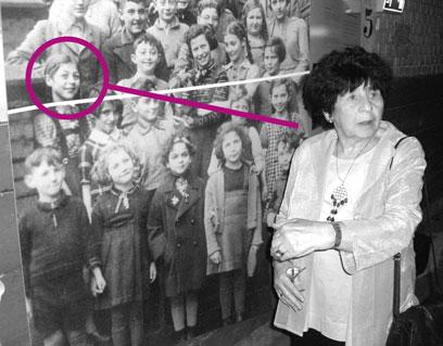 Irmgard Heimbach steht vor einer großen Fotografie mit einigen Schulkindern, eine Markierung zeigt ihr Gesicht auf dem Foto.