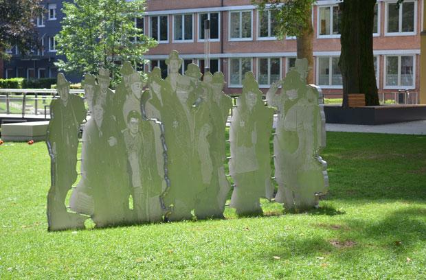 Gruppenbild ausgefräst aus Stahl auf einer Wiese mit Wegen und Gebäuden in der Nähe.