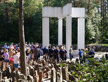 Menschenmasse an einem Denkmal mit vor Säulen und kreuzförmigen Balken der die Säulen verbindet. Im Vordergrund hüfthohe raue Steinsäulen.