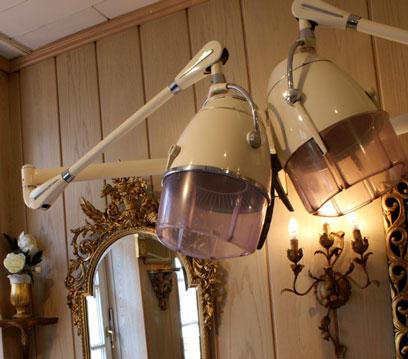 Holzvertäfelter Raum mit Spiegel, Wandleuchter und zwei Trockenhauben aus dem letzten Jahrhundert.
