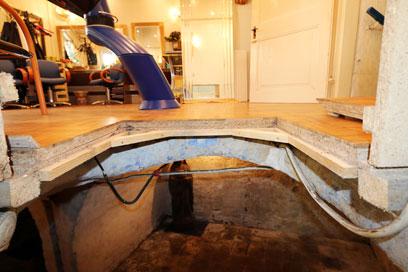 In der Oberen Hälfte der Friseursalon, darunter ein beleuchteter Raum, dazwischen der geöffnete Boden, sichtbarer Querschnitt des Fußbodens und der Steindecke.
