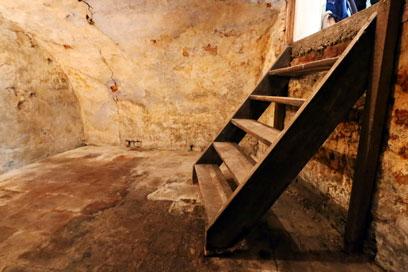 Gekälktes steinernes Gewölbe mit schulterhoher dunkler Holztreppe. Der geflieste Boden ist teils rot, teils hell, teils dunkel.