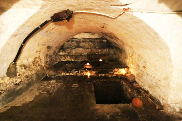 Gekälktes Gewölbe mit Kabeln an der Decke, dunkler Boden und rechteckiger Einlass am rechten Rand.