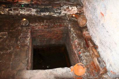 Rechteckiger Einlass aus Klinkern im Boden, der mit wenig Wasser gefüllt ist. An der linken und rechten oberen Ecke Teelichter, an der rechten unteren Ecke ein Gewicht.