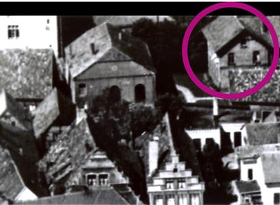 Luftaufnahme, im Vordergrund ein Giebelhaus und Gebäude mit Spitzdach, im Hintergrund ein einstöckiges Gebäude mit mehreren Schornsteinen und großen Bögen, rechts daneben ein zweistöckiges Gebäude mit runder Markierung.