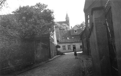 Gepflasterte Straße, links eine Mauer, rechts Mauer und Gebäude, am Ende der Straße ein Kind. Dahinter einstöckiges Gebäude mit Kirchturm darüber.