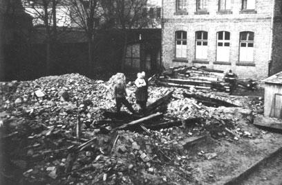 Drei Personen auf Schutt und abgebrannten Holbalken, daneben Ziegelsteingebäude mit großen Fenstern.