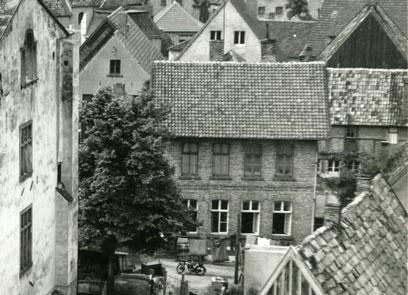 Im Zentrum ein zweistöckiges Gebäude mit Spitzdach, die unteren Fenster geöffnet, umgeben von weiteren Gebäuden.