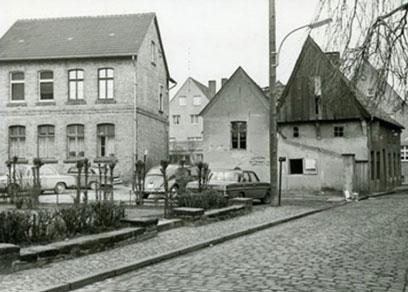 Links zweistöckiges Gebäude mit Spitzdach, davor einige Autos, daneben kleinere einstöckige Gebäude, das rechte mit Holzdach.