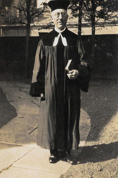 Schwarz-weiß-Fotografie von Hermann Manuel in Gewand mit Brille, in der linken Hand ein Buch. Er steht auf einem Weg mit großen Steinfliesen.