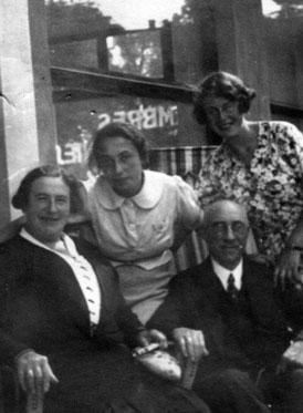 Vier Personen vor einem Fenster, zwei stehend, zwei sitzend.