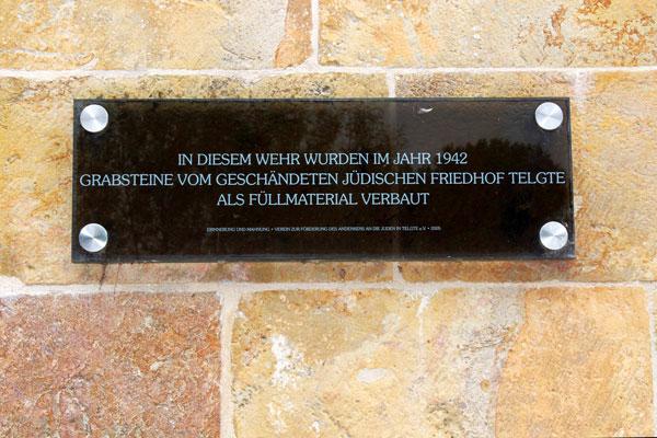 Schwarze Gedenktafel aus Glas mit heller Schrift, befestigt an einer hellen Steinmauer.