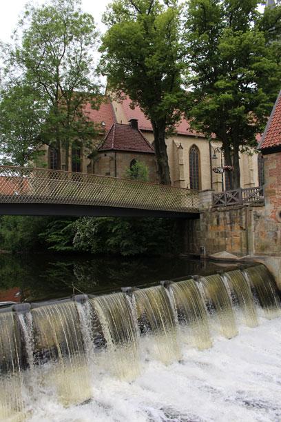 Ein Stauwehr mit fließendem Wasser, unterhalb einer Brücke. Im Hintergrund eine Kirche.