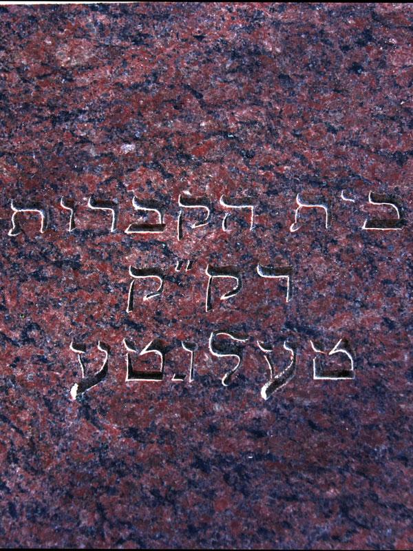 Eine Gedenkplatte aus rotem Marmor mit hebräischer Aufschrift.