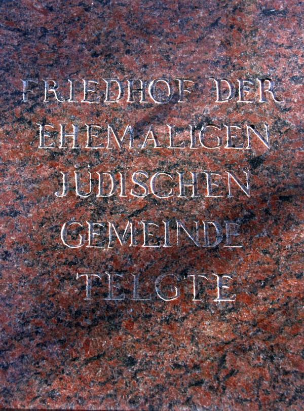 """Gedenkplatte aus rotem Marmor mit der Aufschrift """"Friedhof der Ehemaligen Jüdischen Gemeinde Telgte"""" in Großbuchstaben."""