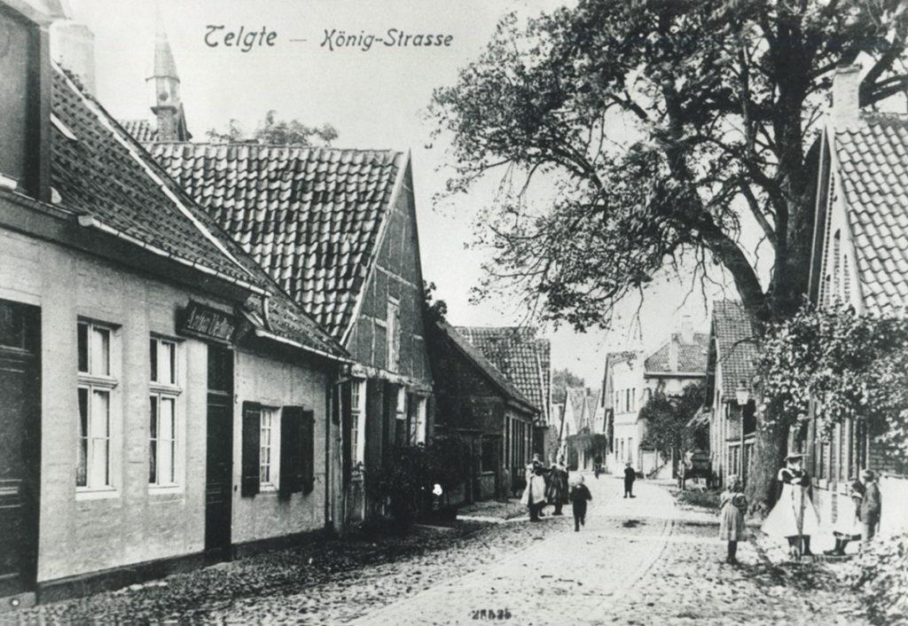 """Ansichtskarte mit einstöckigen Häusern an einer gepflasterten Straße. Oben die Überschrift """"Telgte – König-Strasse"""", daneben ist ein Turm zu erkennen."""