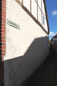 """Schild an einem weiß-verputzen Gebäude mit der Aufschrift """"Judengängsken""""."""