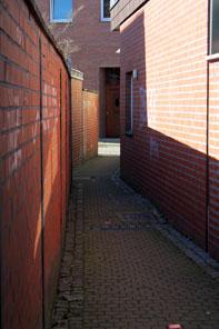 Schmale Gasse zwischen einer roten Backsteinmauer und einem Backsteingebäude.