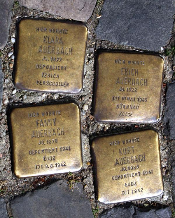 Vier messingfarbene Stolpersteine für Klara, Erich, Fanny und Kurt Auerbach im Kopfsteinpflaster eingelassen.