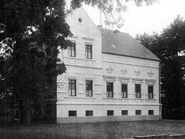 Großes Gebäude, der linke Teil zweistöckig und mit Spitzdach.