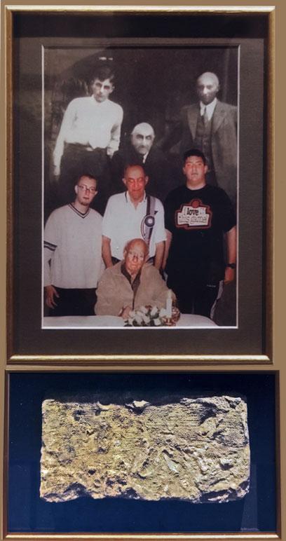 Foto, im oberen Teil drei Männer in schwarz-weiß, darunter drei stehende und ein sitzender Mann in Farbe. Darunter ein creme-farbener rechteckiger Stein mit blauem Hintergrund.