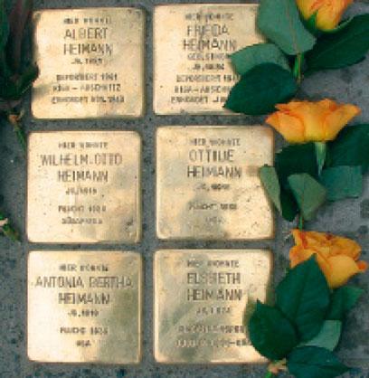 Sechs Stolpersteine mit drei orangenen Rosen an der rechten Seite.