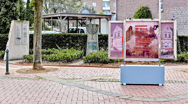 Gepflasterte Straße, links eine Wand mit zwei Infotafeln, mittig im Hintergrund ein Gedenkstein mit Menora-Relief, rechts ein geöffneter Fensterrahmen befestigt auf einem kniehohen Unterbau, anstelle von Glas sind Bilder und Texte eingesetzt Bild 11 Links unten eine Kiste abgedeckt, darüber der Fensterrahmen, rechts ein Modell eines einstöckigen Gebäudes mit blauer Fassade und rotem Walmdach