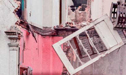 Abriss eines Gebäudes, ein Fenster hängt nur noch an einem Stein.