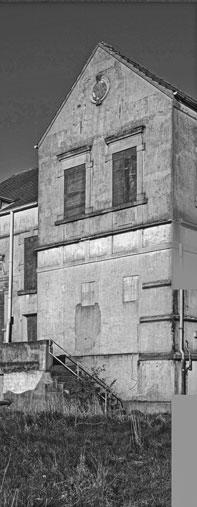 Weitere Ansicht des Gebäudes, sowohl die Fenster des ersten als auch zweiten Stockes sind durch Bretter verschlossen.