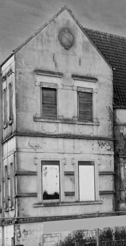 Schwarz-weiß-Aufnahme eines zweistöckigen Gebäudes, die Tür ist zugemauert, die Fenster verbrettert.