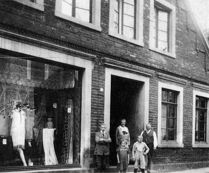 Fünf Personen vor einem großen Eingang eines Gebäudes. Links davon ein Schaufenster mit Schaufensterpuppen und Kleidungsstücken.
