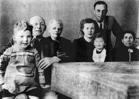 7 Personen sitzend/stehend vor einem Tisch, darunter zwei Kinder.