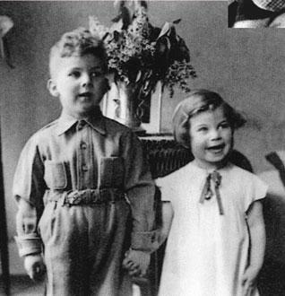 Die Kinder nebeneinanderstehend und händchenhaltend stehen vor einer Vase und schauen rechts an der Kamera vorbei.