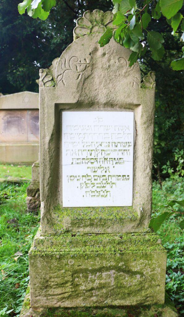Hoher Grabstein aus hellem Stein, eine Platte in der Mitte eingelassen aus hellem Stein mit eingemeißelter hebräischer Schrift.