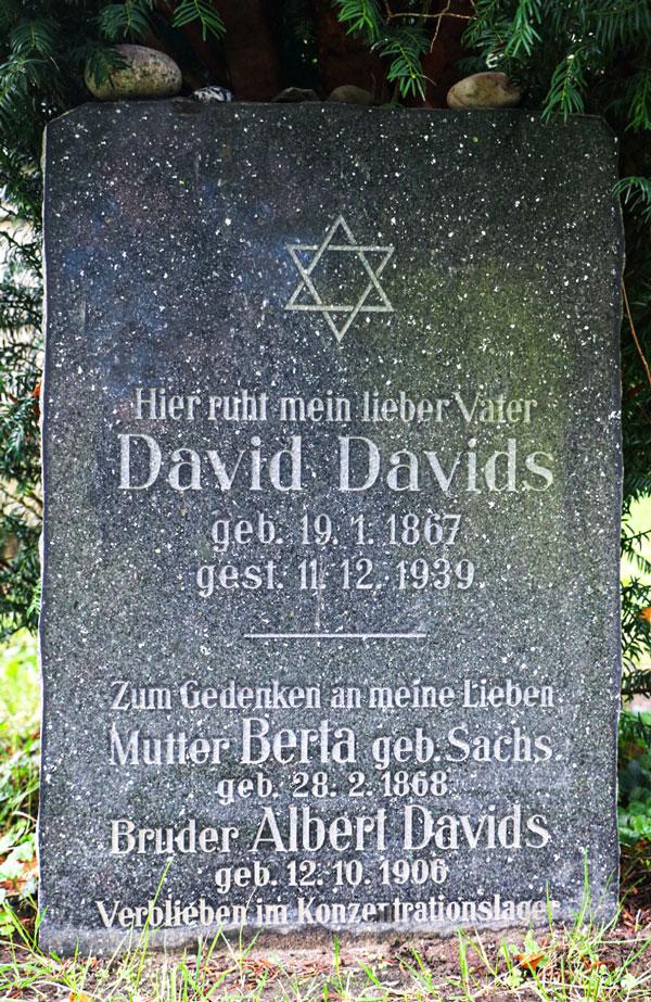Schwarzer Grabstein mit eingemeißelter Schrift. Im oberen Teil ein Davidstern.