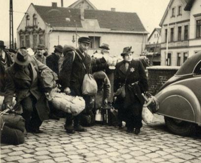 Schwarz-weiß-Aufnahme vieler Personen, bepackt mit Bettzeug, Beuteln und Koffern. Im Hintergrund ein großes Gebäude.