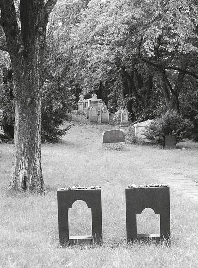 Zwei kniehohe Platten, darin ausgeschnitten ein großes und ein kleines Fenster, im Hintergrund ein Baum und Grabsteine. Auf den Platten liegen einige Steine.